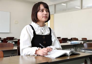 画面を指差しながら学生に指導する教授